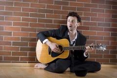 O homem de negócios senta o canto com a guitarra no assoalho Fotos de Stock Royalty Free