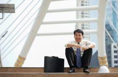 O homem de negócios senta-se felizmente rindo da passagem moderna da escada Imagens de Stock