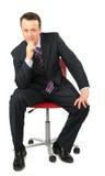 O homem de negócios senta-se na cadeira do escritório Imagem de Stock Royalty Free