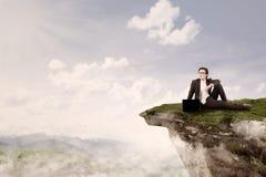 O homem de negócios senta-se sobre a montanha Foto de Stock Royalty Free