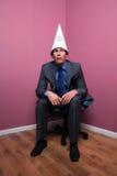 O homem de negócios sentou-se no chapéu desgastando de canto do burro imagens de stock royalty free