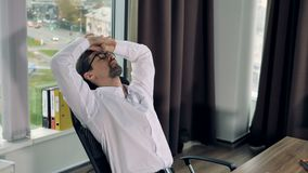 O homem de negócios sobrecarregado estica seus braços durante o trabalho vídeos de arquivo