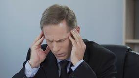 O homem de negócios sofre da dor de cabeça doente, problema no trabalho, esforço de sobrecarregar filme