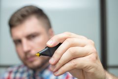O homem de negócios Startup tira com um marcador amarelo no vidro durante uma reunião no escritório Fotografia de Stock