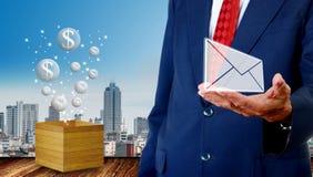 O homem de negócios superior leva o e-mail com o flutuador do ícone das bolhas do dinheiro da caixa de madeira ao lado, fotos de stock
