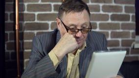 O homem de negócios superior nos monóculos está trabalhando com uma tabuleta digital no escritório ilustração do vetor