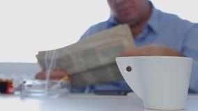 O homem de negócios Taking um jornal lido ruptura fuma um cigarro e para beber um café fotografia de stock royalty free