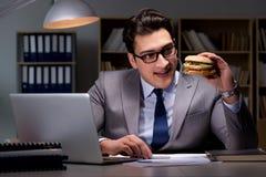 O homem de negócios tarde na noite que come um hamburguer Fotografia de Stock Royalty Free