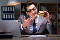 O homem de negócios tarde na noite que come um hamburguer Fotos de Stock Royalty Free