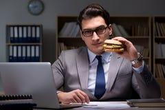 O homem de negócios tarde na noite que come um hamburguer Fotos de Stock