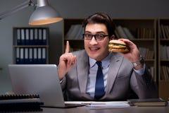 O homem de negócios tarde na noite que come um hamburguer Imagem de Stock