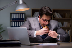 O homem de negócios tarde na noite que come um hamburguer Foto de Stock Royalty Free