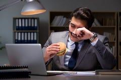 O homem de negócios tarde na noite que come um hamburguer fotografia de stock