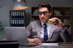 O homem de negócios tarde na noite que come um hamburguer Imagens de Stock Royalty Free