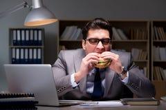 O homem de negócios tarde na noite que come um hamburguer Imagens de Stock