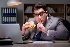 O homem de negócios tarde na noite que come um hamburguer Imagem de Stock Royalty Free