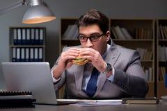 O homem de negócios tarde na noite que come um hamburguer Foto de Stock