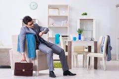 O homem de negócios tarde para o escritório devido a dormir demais após o trabalho durante a noite Foto de Stock
