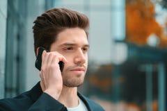 O homem de negócios tem a conversação séria usando o telefone celular Indivíduo do negócio em negociações formais do terno atenta imagem de stock royalty free