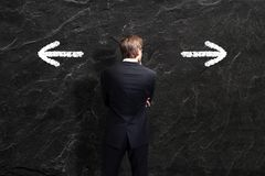O homem de negócios tem que decidir entre dois sentidos Foto de Stock Royalty Free