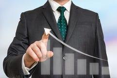 O homem de negócios tira um gráfico em um tela táctil virtual Fotografia de Stock Royalty Free