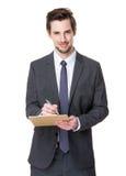 O homem de negócios toma a nota na prancheta foto de stock royalty free