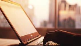 O homem de negócios trabalha em um portátil pela janela grande nas construções da cidade durante tipos do por do sol no teclado F vídeos de arquivo