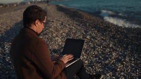 O homem de negócios trabalha na praia vídeos de arquivo