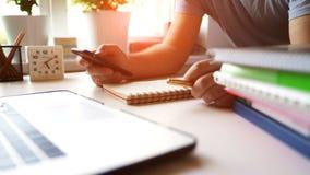 O homem de negócios usa um smartphone e um portátil no escritório no local de trabalho na luz solar da manhã vídeos de arquivo