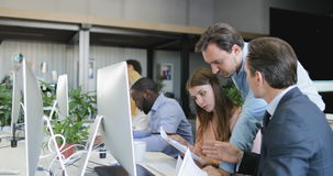 O homem de negócios vem ajudar executivos a tratar os originais que trabalham no espaço de escritórios criativo, trabalhos de equ video estoque