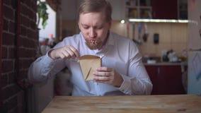 o homem de negócios Vermelho-farpado come os macarronetes imediatos muito quentes e picantes video estoque