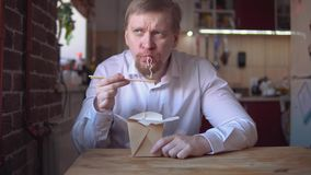 o homem de negócios Vermelho-farpado come os macarronetes imediatos muito quentes e picantes vídeos de arquivo