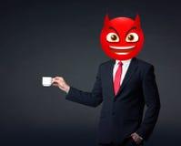 O homem de negócios veste a cara do smiley do diabo Imagens de Stock