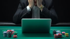O homem de negócios viciado de jogo na frente do portátil, aposta perdedora do esporte, fale video estoque