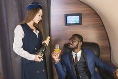 O homem de neg?cios afro-americano bem sucedido novo nos vidros e em uma comiss?ria de bordo mostra uma garrafa do vinho na cabin foto de stock royalty free