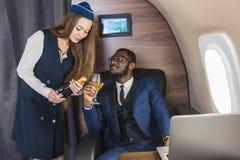 O homem de neg?cios afro-americano bem sucedido novo nos vidros e em uma comiss?ria de bordo mostra uma garrafa do vinho na cabin imagens de stock royalty free