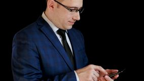 O homem de neg?cios em um terno trabalha com um smartphone, toca no tela t?ctil do telefone foto de stock