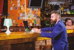 O homem de neg?cios farpado do homem senta o bar com port?til e x?cara de caf? Trabalho do gerente em linha quando aprecie o caf? imagem de stock