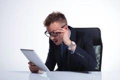 O homem de negócio olha sua tabuleta com incrédulo Fotos de Stock