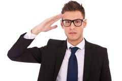 O homem de negócio que desgasta vidros dá a saudação Fotografia de Stock