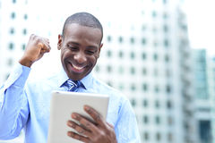 O homem de negócios comemora seu sucesso com tabuleta Foto de Stock Royalty Free