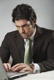 O homem de negócios considerável olha o laptop Foto de Stock Royalty Free