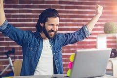 O homem de negócios criativo de sorriso com braços levantou a vista do portátil Fotografia de Stock Royalty Free