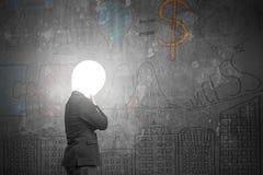 O homem de negócios de pensamento com negócio escuro iluminado cabeça da lâmpada faz Fotografia de Stock