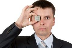 O homem de negócios fecha um olho, um processador Fotos de Stock Royalty Free