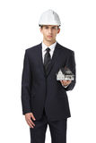 O homem de negócios no capacete entrega a casa modelo Imagem de Stock Royalty Free