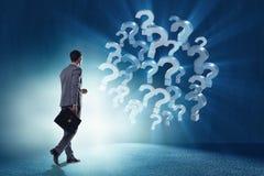 O homem de negócios no conceito da incerteza com pontos de interrogação Imagem de Stock Royalty Free