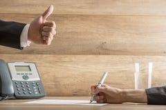 O homem de negócios que expressa sua aprovação fazendo os polegares levanta o gestur Imagens de Stock