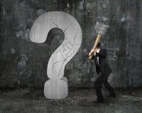 O homem de negócios que guarda o martelo rachou o ponto de interrogação com mottl escuro Fotografia de Stock