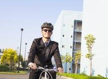 O homem de negócios que monta uma bicicleta ao local de trabalho para proteger cerca Imagem de Stock